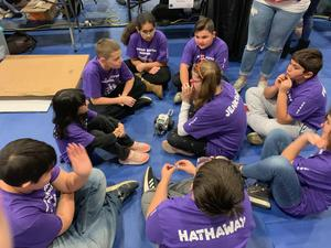 Students in their purple team t-shirts sitting on the floor with their robot