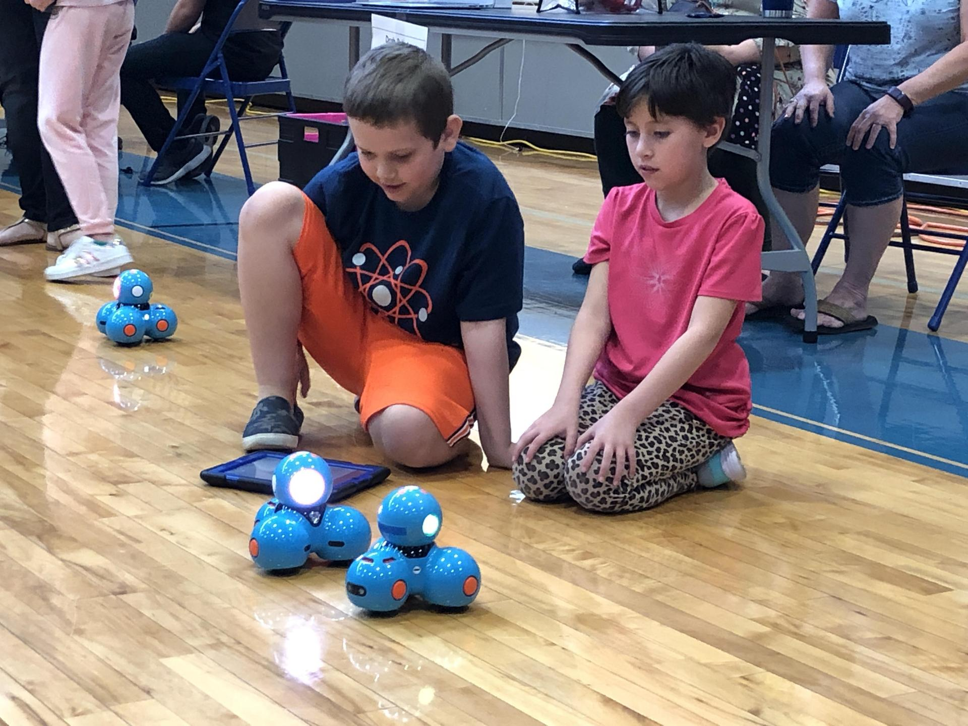 Students using coding skills to manipulate a robot.