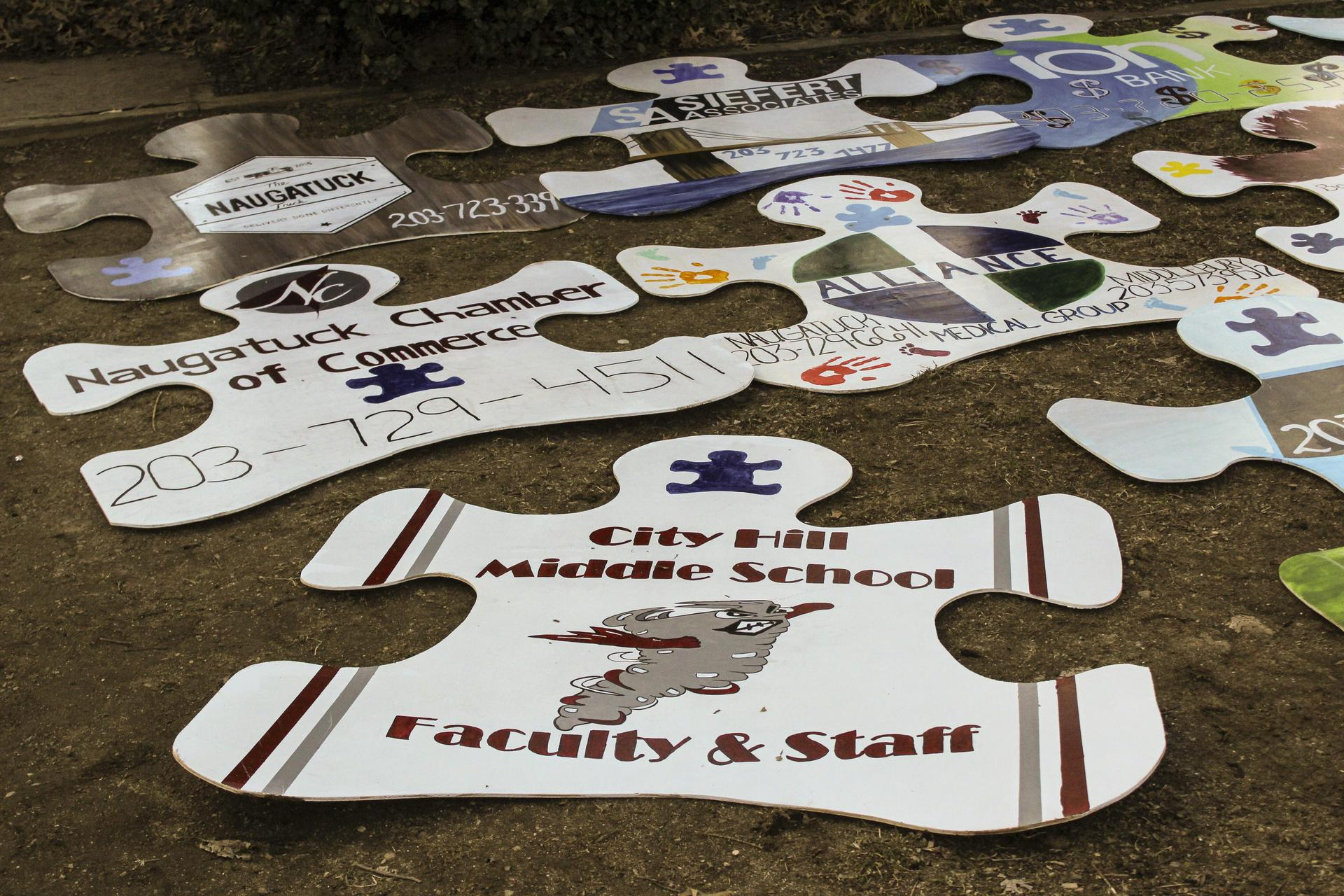 Giant wooden puzzle pieces with sponsor logos including City Hill Middle School Faculty & Staff