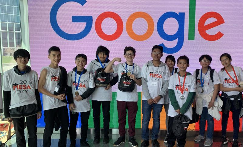 eight students standing in front of Google sign