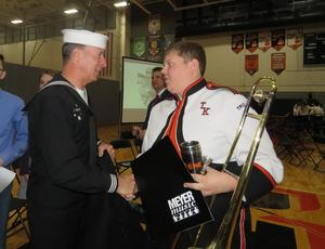 A TKHS student shakes hands with Middleville's Veteran of the Year Bob Buys.