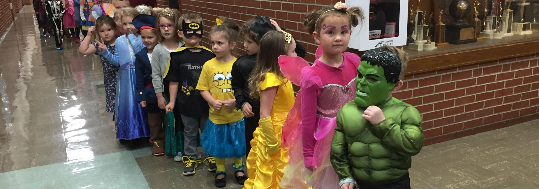 Students dressed in Halloween costumes parading down hallway