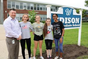 From left, Edison Intermediate School principal Dr. Matthew Bolton congratulates 8th grader Grabriela Gil and 7th graders Sofia Gil, Hannah Hollosi and Anusha Iyer who are finalists in a national STEM competition.
