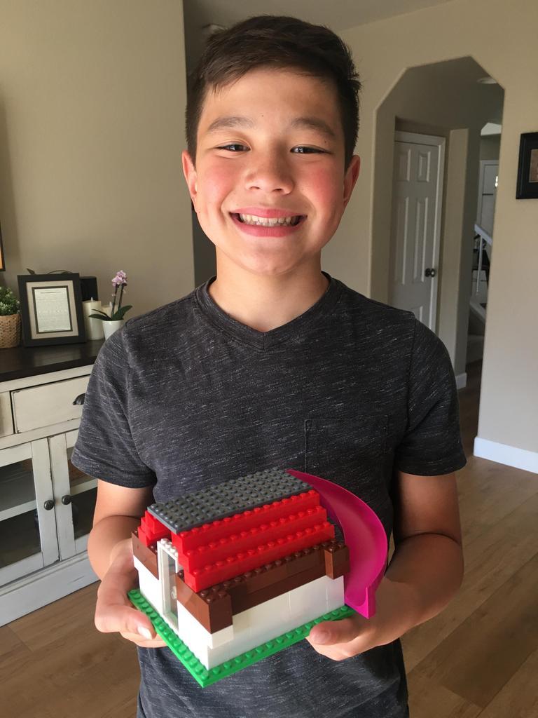 boy holding lego house