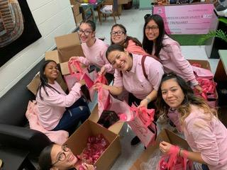 students smiling as they take the pink bags