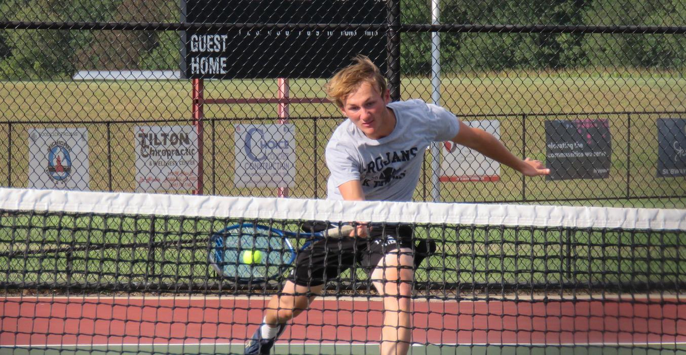 A TKHS varsity tennis player rushes the net to return a volley.