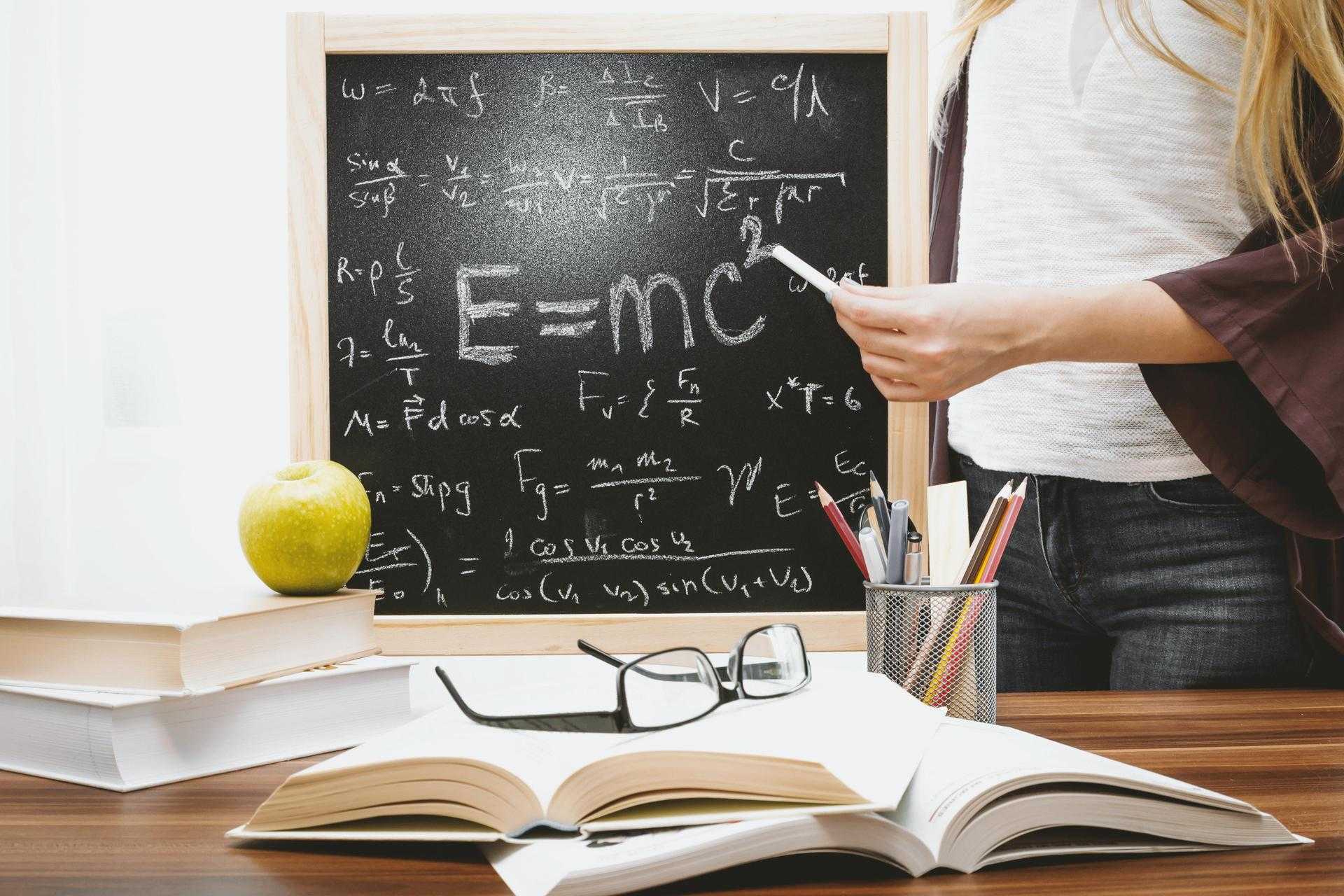 Photo of a teacher and chalkboard