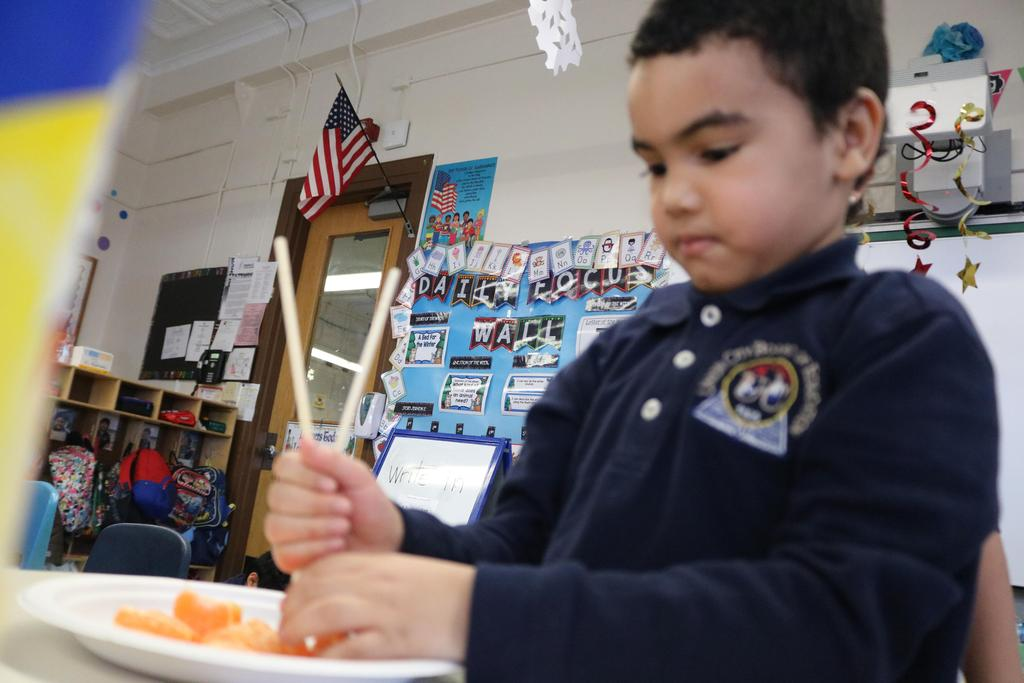 boy trying to eat tangerine piece with chopsticks