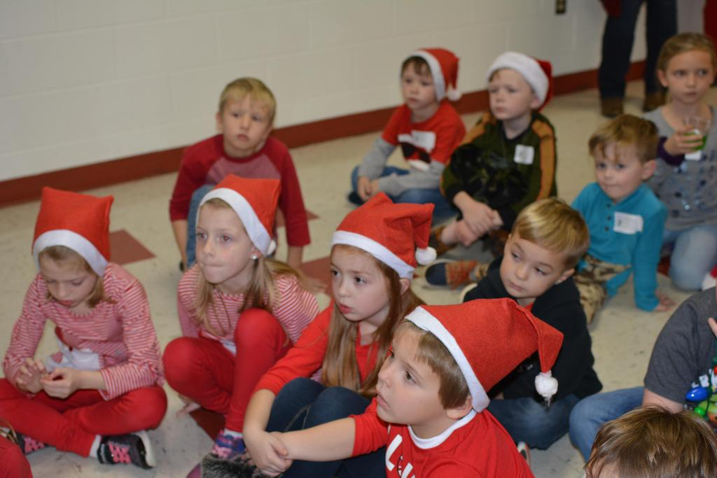 First grade students listening to a story on Grinch night