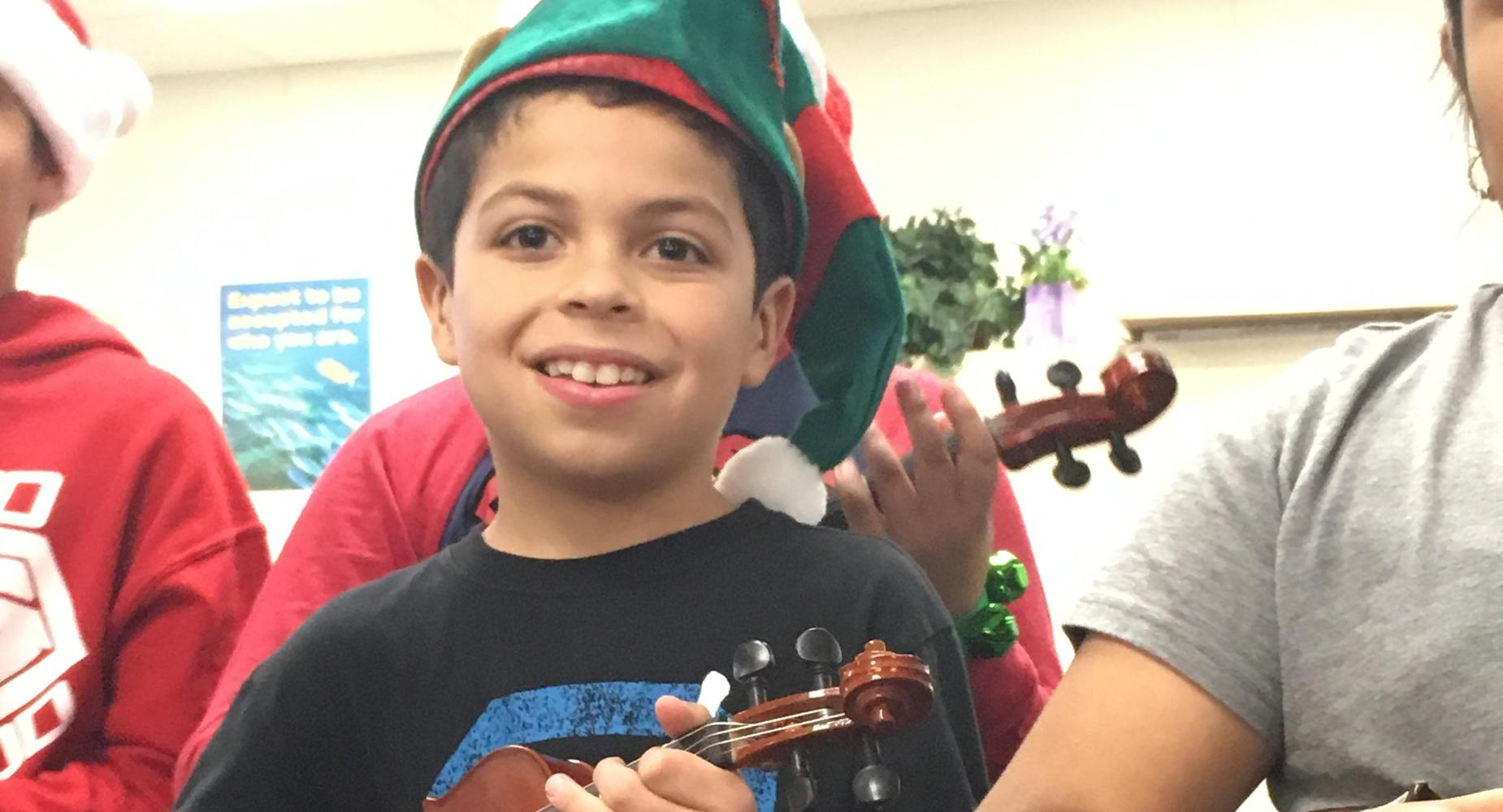 A student from Choices playing the violin for the Roosevelt staff.