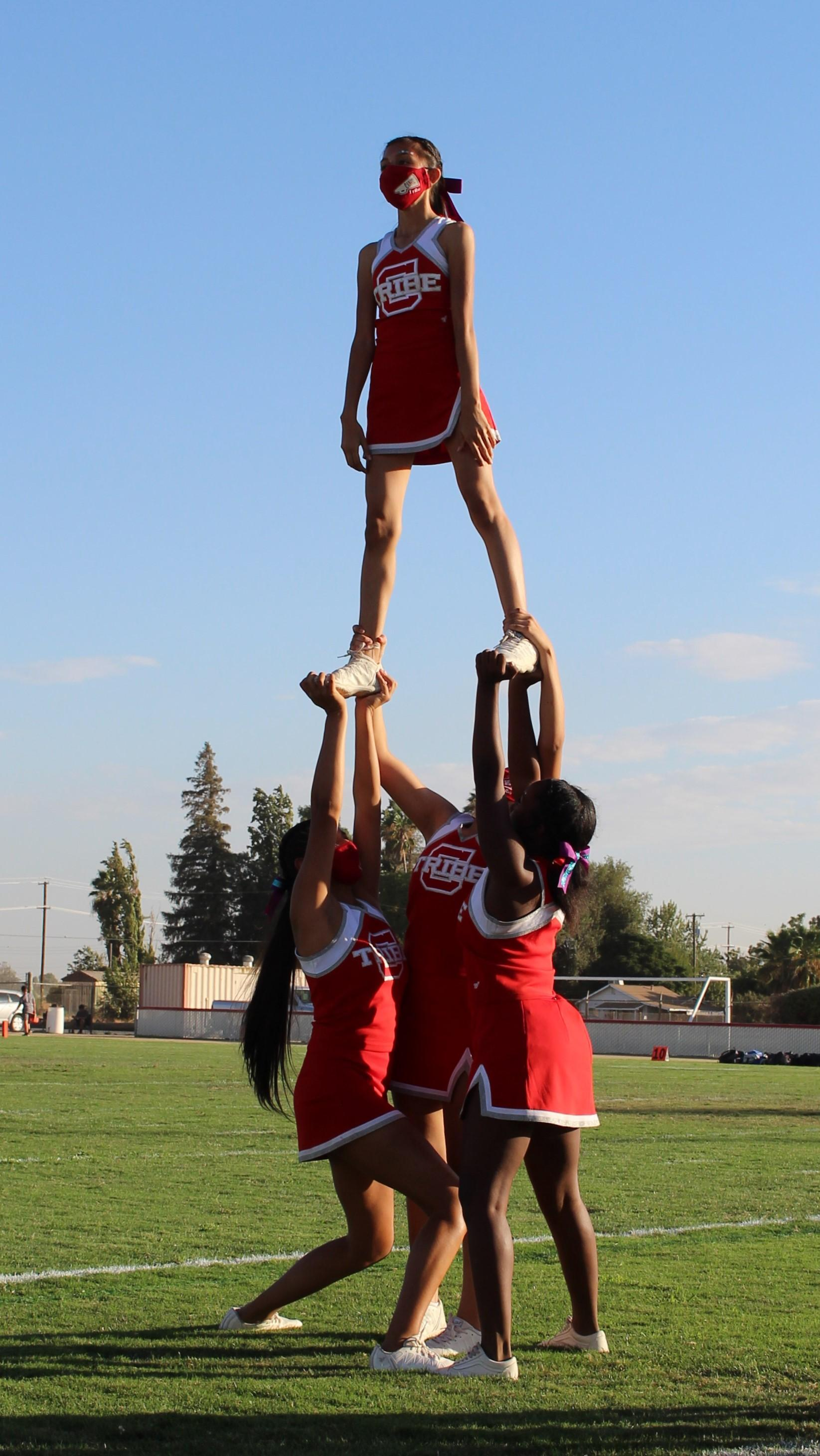 Cheerleaders cheering at the JV football game against central valley christian