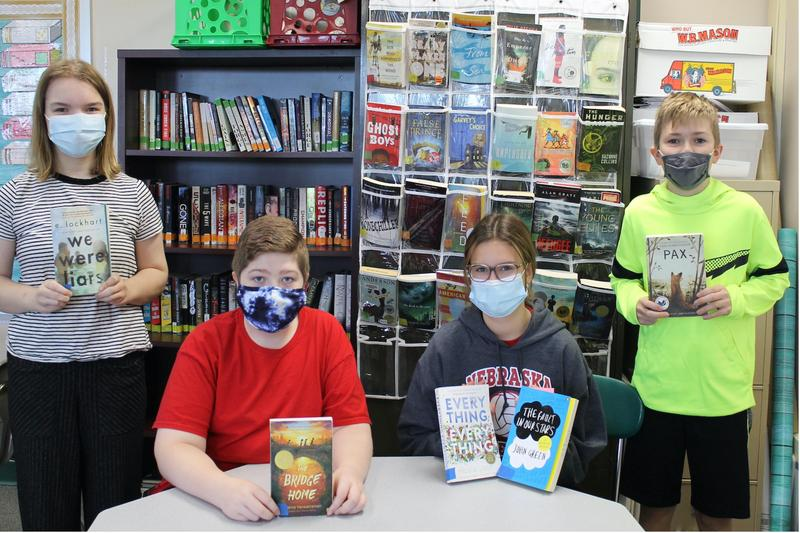 students holding some of the new books