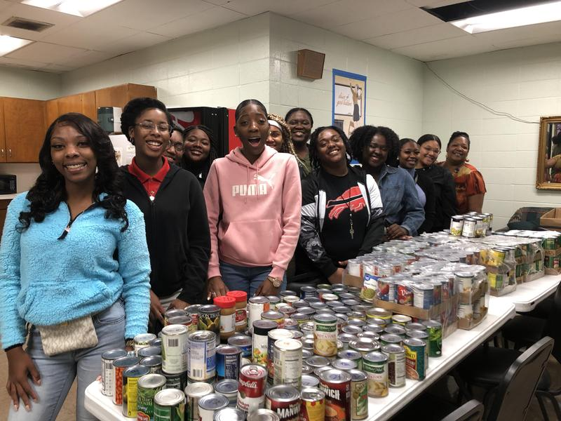 A photo of Baker High Students and Sponsors who worked with the collection of canned goods for holiday gift