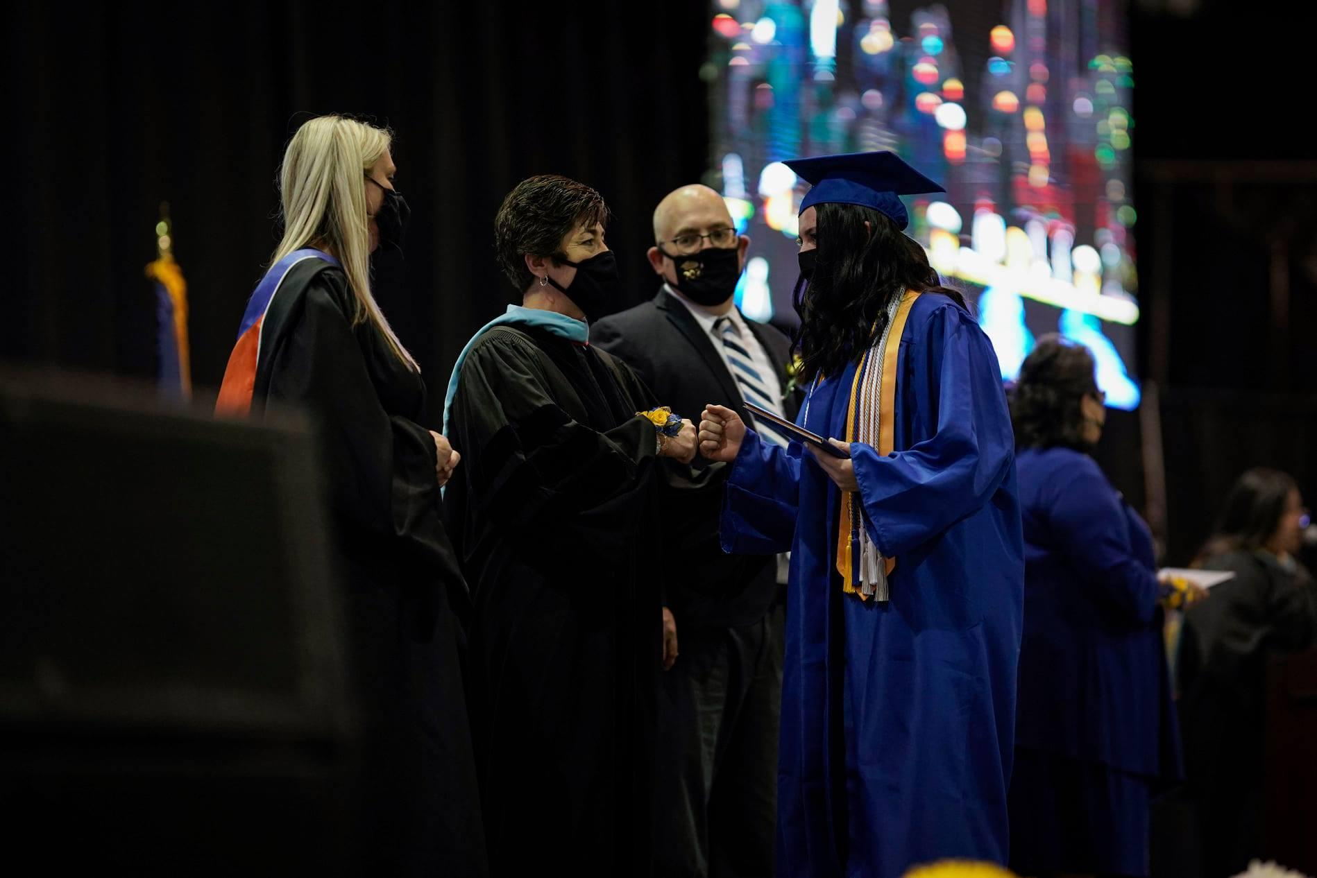 Superintendent French hands diploma