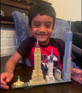 Boy in front of city buildings toy