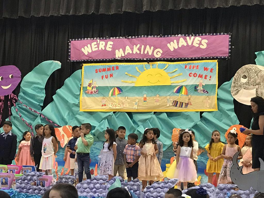 kids singing and dancing on a decorated sea theme stage