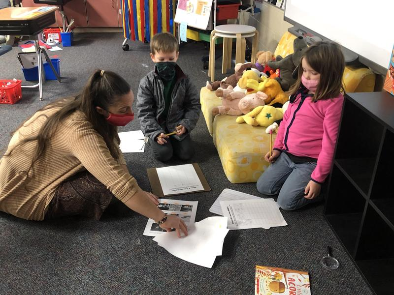 Teacher working with kids on books.