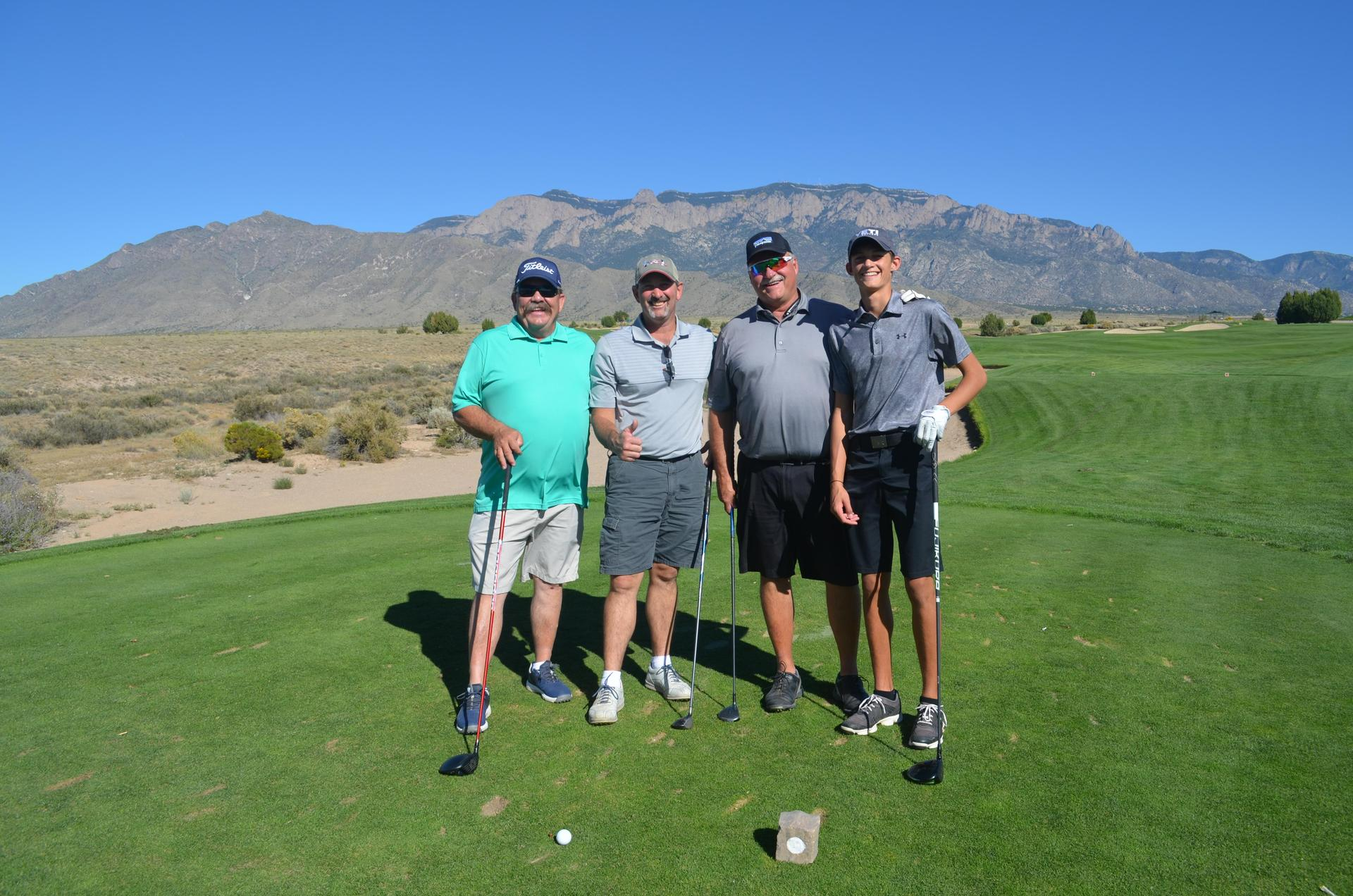 Golfers smile in front of Sandia Mountains on golf course