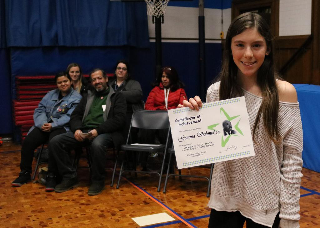 Photo of Wilson 5th grade winner of MLK Jr Essay contest, showing her certificate.