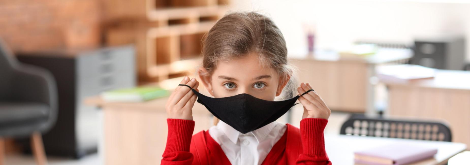 girl putting on mask