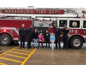 4 students pose with 4 firemen in front of firetruck