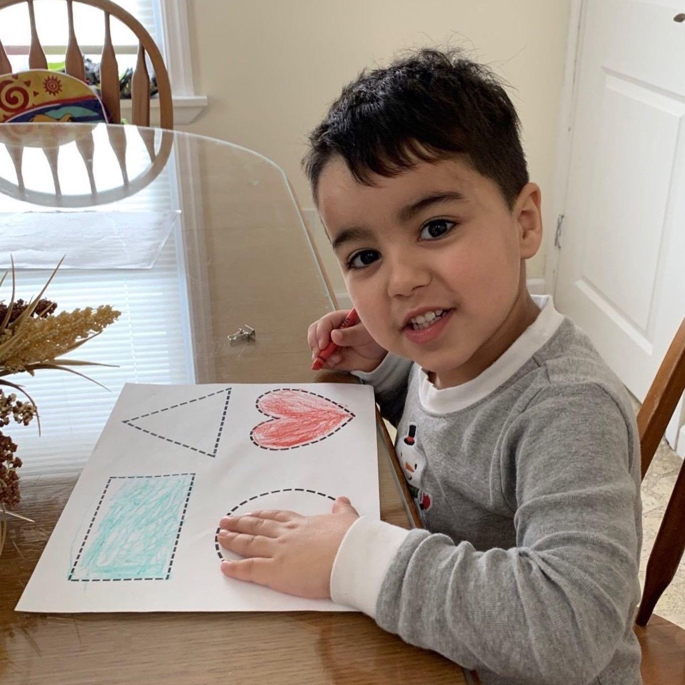 boy coloring his shape activity sheet