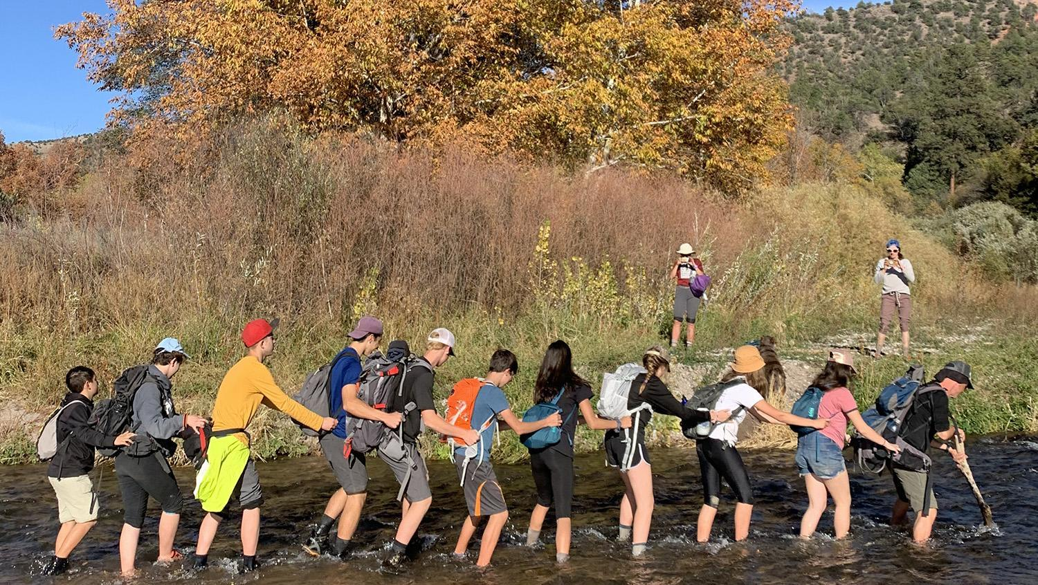 Line of students crossing river