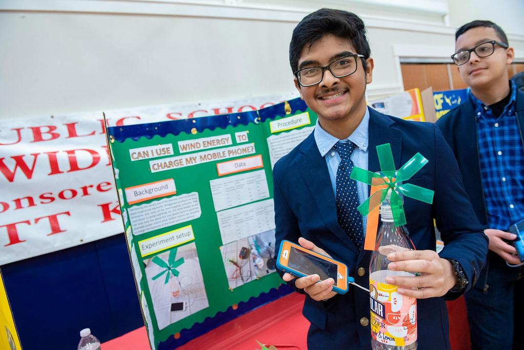 A student holds a small, handmade windmill and a cellphone