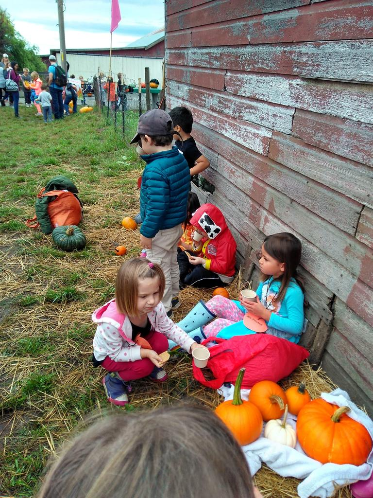 Children sitting and eating snack infront of a barn