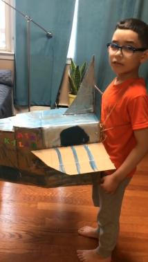 boy with glasses showing off his box plane