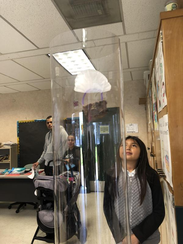 A student watches her engineering creation in a wind tunnel.