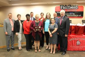 The image shows teacher Kim Witt holding her award from the school board. school board members and Superintendent Billy Smith are standing with her for the photo.
