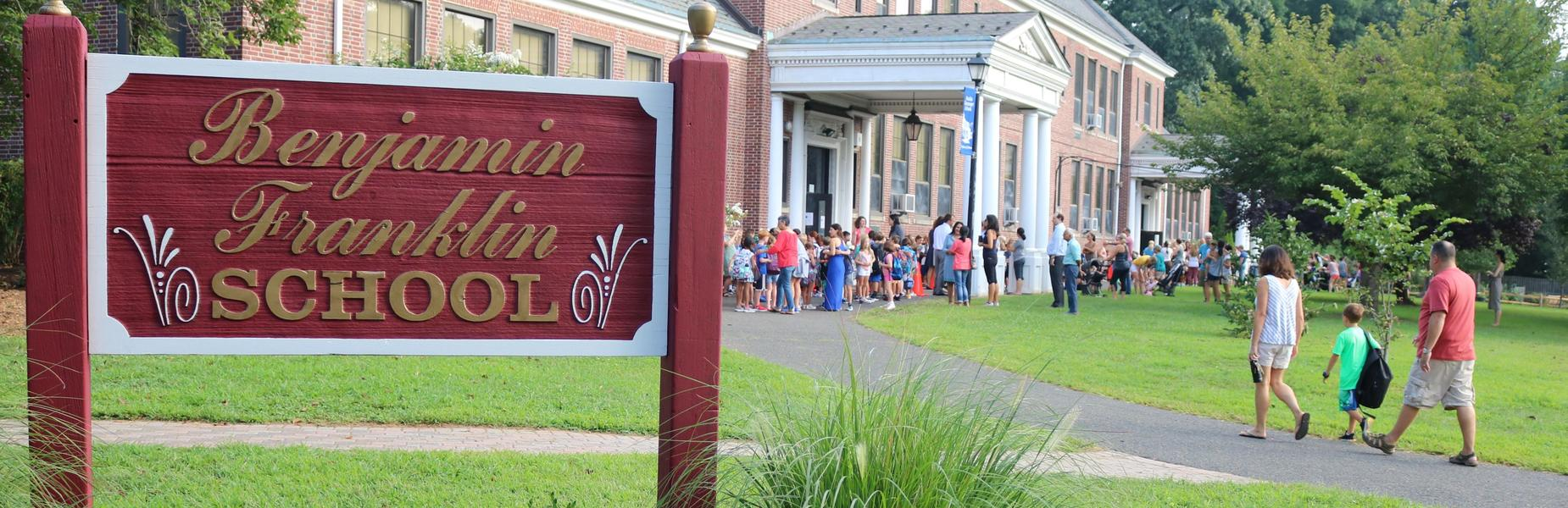 Photo of Franklin School sign with students and families arriving for start of a new school year.