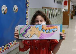 Photo of Franklin 2nd grader showing her watercolor painting of a Chinese dragon.