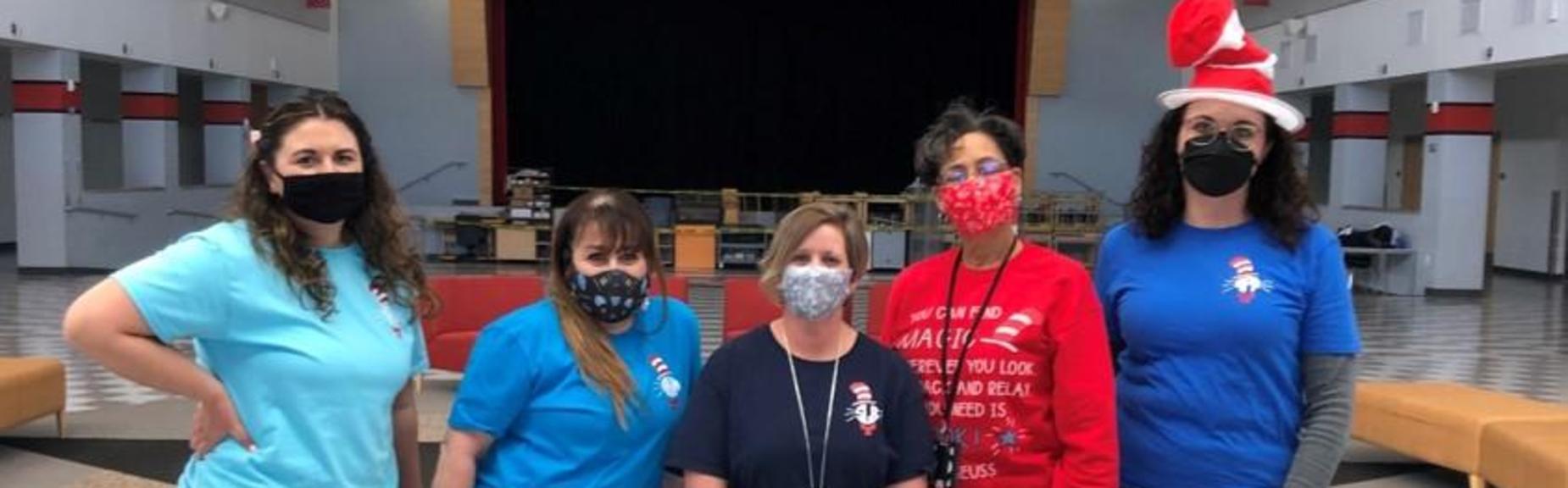Five ladies wearing masks.