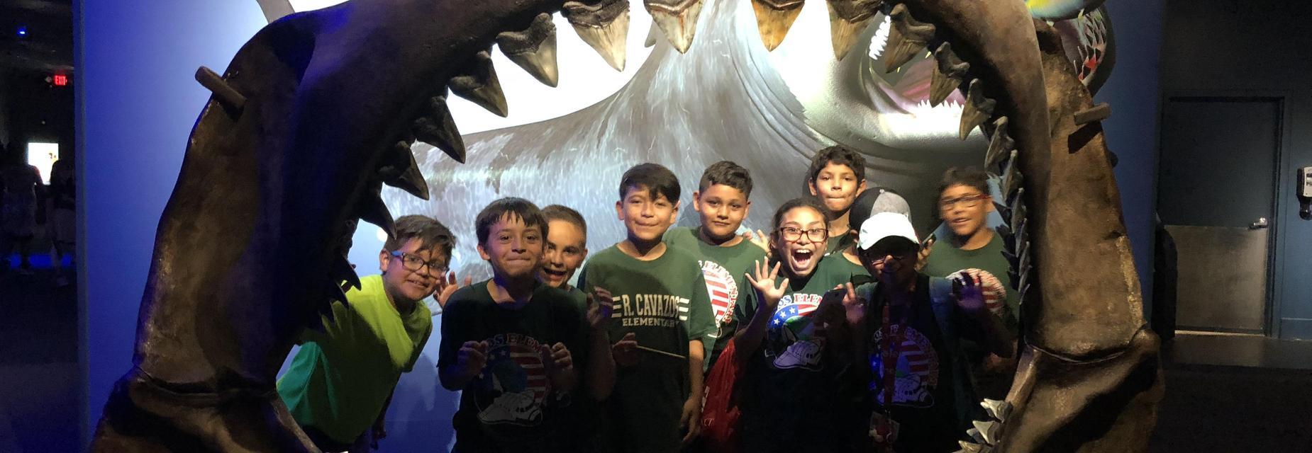 students inside of shark mouth skeleton