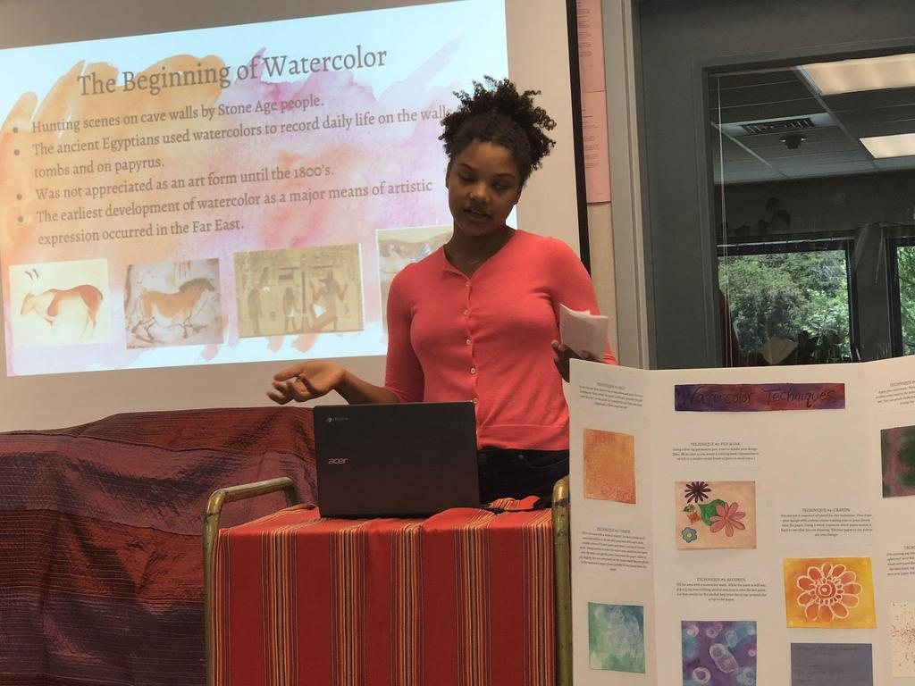 Student presenting on watercolor drawings.