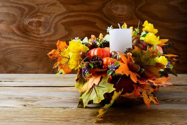 Centerpiece made of multicolored leaves on a wood table.