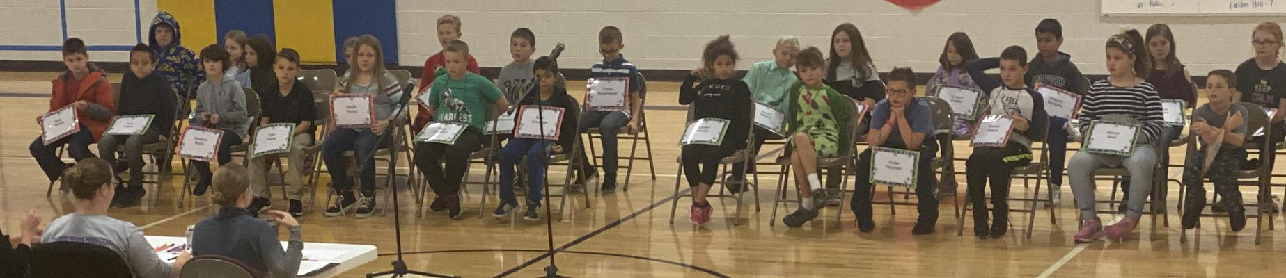 Students sitting in chairs on gym floor, participating in the spelling bee