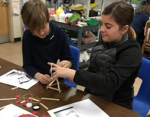 Jefferson 5th graders Oscar Bird (left) and Alyssa Catalano design, build and test a simple catapult using rubber bands, popsicle sticks and bottle caps during makerspace activities in early March.