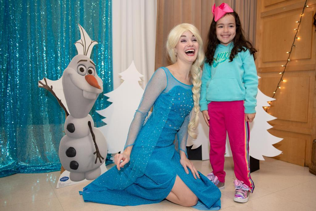 """Elsa from """"Frozen"""" kneels next to a student"""