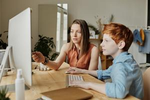 Student and parent working on computer at home.