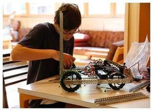 boy working on robotics project on table