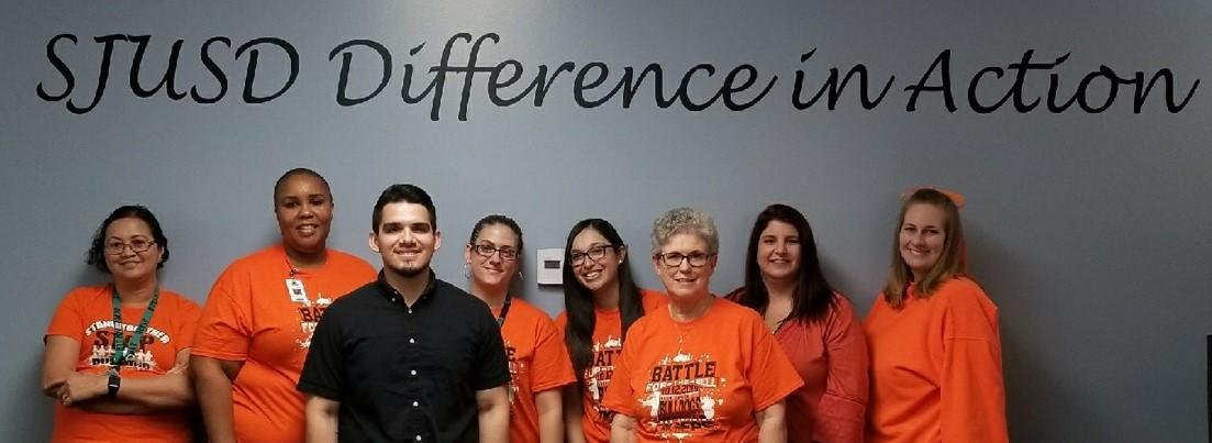 Business Department staff participating in 'Battle of the Bell' week, wearing SJHS Tigers orange and black