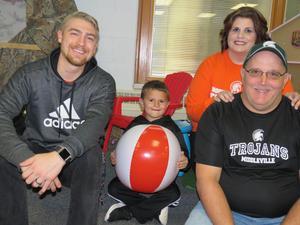 Joey Graham sits beside his kindergarten teacher Mr. Bultema and his parents Dawn and Joe Graham.