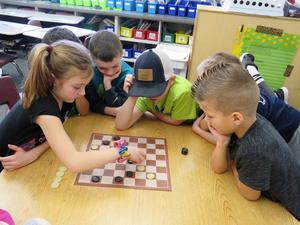 This group of first-grade students are engaged in a game of checkers.