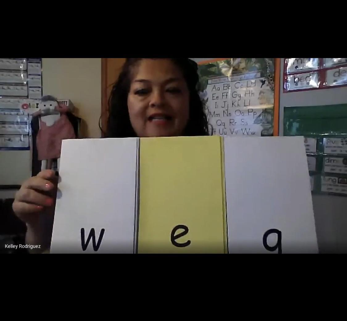 A teacher holds up W E A