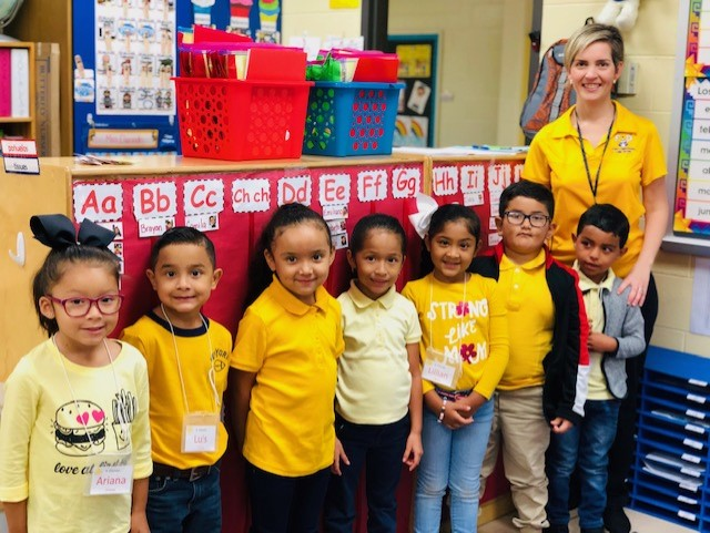 Kinder teacher with students in all yellow for Homecoming Week