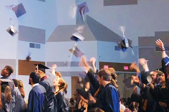High school graduates throwing graduation caps in the air