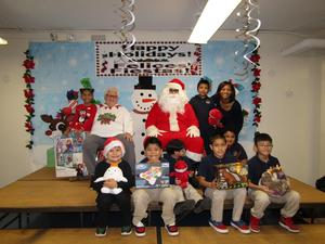 first grade class taking photo with Santa showing off their gifts